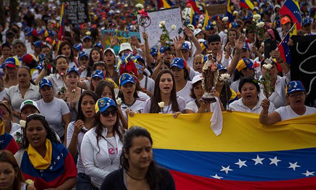 Um grupo de maioria mulheres marcham carregando rosas e bandeira venezuelana, pedindo paz e não-violência em San Cristobal, Venezuela, 26 de fevereiro de 2014. (Foto: Meridith Kohut / The New York Times)..